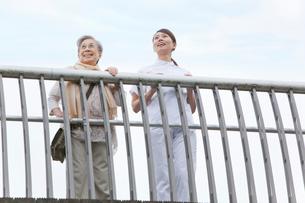 橋の上から遠くを見つめるシニア女性と女性介護士の写真素材 [FYI02069693]