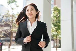 髪の毛をなびかせてオフィス街を走るスーツ姿の女性の写真素材 [FYI02069700]