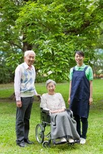 笑顔でこちらを見る女性介護士とシニア男女の写真素材 [FYI02069701]
