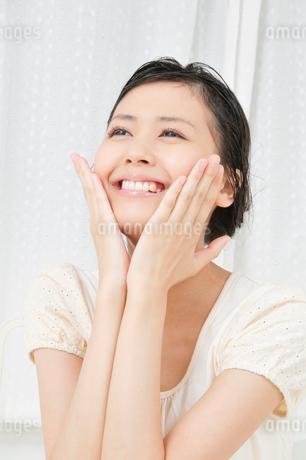 両手で顔をマッサージする若い女性の写真素材 [FYI02069711]