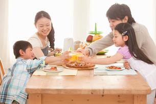 オレンジジュースで乾杯をする4人家族の写真素材 [FYI02069719]