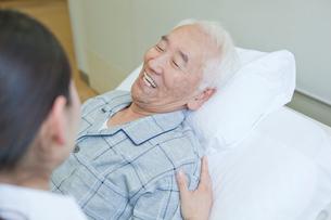 ベッドで横になり女性と会話をするシニア男性の写真素材 [FYI02069722]