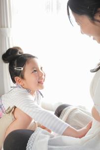母親のおなかをやさしく触る女の子の写真素材 [FYI02069727]
