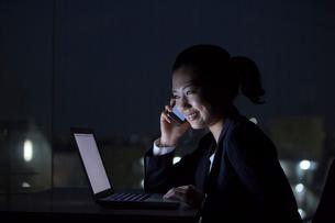 暗闇で携帯電話で話すスーツ姿の女性の写真素材 [FYI02069728]