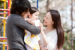 公園で赤ちゃんを抱く父親と笑顔で寄り添う母親の写真素材 [FYI02069731]
