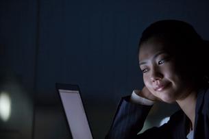 暗闇でノートパソコンを見るスーツ姿の女性の写真素材 [FYI02069734]