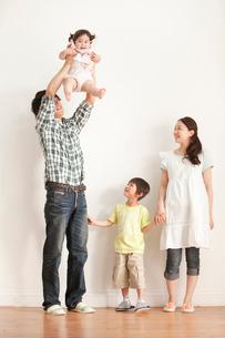 赤ちゃんを抱き上げる父親を笑顔で見守る母親と息子の写真素材 [FYI02069757]