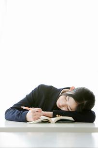 ペンを持ったまま居眠りをする女子高校生の写真素材 [FYI02069774]