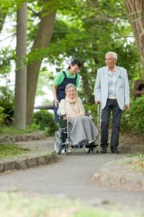 公園を散歩するシニアカップルと女性介護士の写真素材 [FYI02069776]