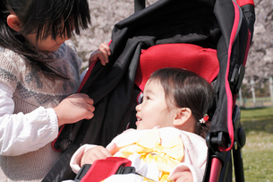 ベビーカーに乗った赤ちゃんに話しかける女の子の写真素材 [FYI02069784]