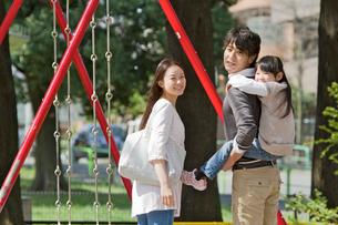 子供を背負って公園を散歩する3人家族の写真素材 [FYI02069793]