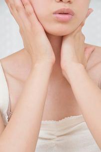 両手で顔をマッサージする若い女性の写真素材 [FYI02069795]