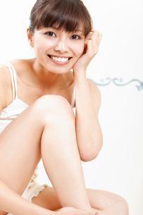 立て膝で座る若い女性の写真素材 [FYI02069801]