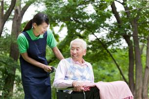 シニア男性の乗った車いすを押す女性介護士の写真素材 [FYI02069802]