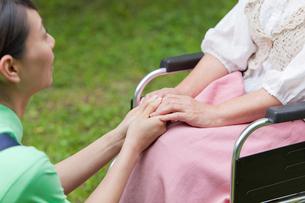 車いすに乗ったシニア女性の手を握る女性介護士の写真素材 [FYI02069807]