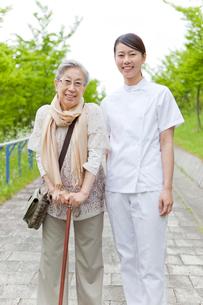 笑顔でこちらを見る女性介護士とシニア女性の写真素材 [FYI02069815]