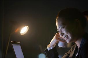 缶ビールを手にノートパソコンを見るスーツ姿の女性の写真素材 [FYI02069816]