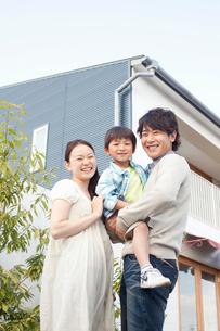 家の前で息子を抱き寄り添う若い夫婦の写真素材 [FYI02069820]