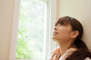 窓際で天井を見上げる若い女性の横顔の写真素材 [FYI02069830]