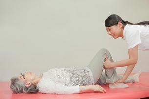 リハビリ施設でシニア女性の介助をする女性介護士の写真素材 [FYI02069831]