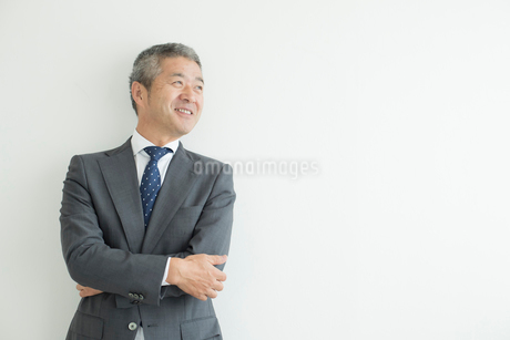 壁を背に立つミドルビジネスマンの写真素材 [FYI02069846]