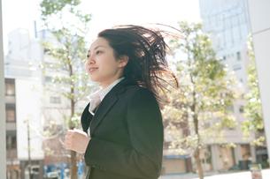 髪の毛をなびかせてオフィス街を走るスーツ姿の女性の写真素材 [FYI02069847]