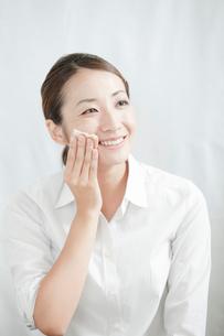 化粧落としで顔を拭く若い女性の写真素材 [FYI02069859]