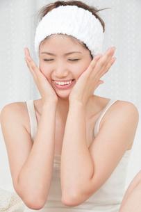 両手で顔をマッサージする若い女性の写真素材 [FYI02069866]