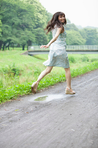 水たまりをジャンプする若い女性の写真素材 [FYI02069867]