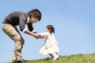赤ちゃんの手を引き歩かせる父親の写真素材 [FYI02069880]