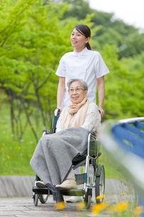 公園を散歩する車いすに乗ったシニア女性と女性介護士の写真素材 [FYI02069884]