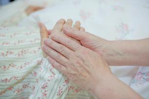 ベッドで横になるシニア女性の手を握るシニア女性の写真素材 [FYI02069885]