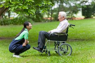 車いすに乗った男性と話す女性介護士の写真素材 [FYI02069899]