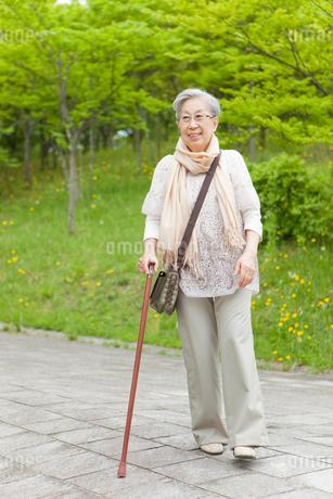 公園を散歩する杖をついたシニア女性の写真素材 [FYI02069903]