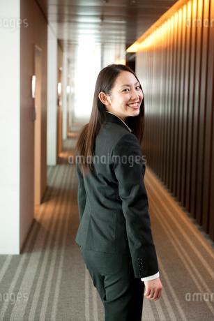 オフィスの廊下で笑顔で振り返るスーツ姿の女性の写真素材 [FYI02069916]