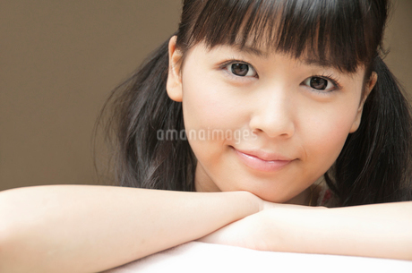 組んだ手にあごを乗せこちらを見つめる若い女性の写真素材 [FYI02069927]
