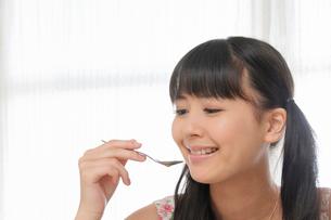 窓際でスープを飲む若い女性の写真素材 [FYI02069934]