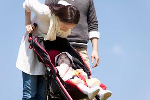ベビーカーに乗った赤ちゃんに話しかける若い母親の写真素材 [FYI02069939]