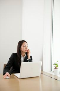 オフィスでノートPCを使い仕事をしている女性の写真素材 [FYI02069942]