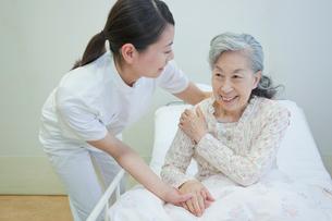 ベッドで横になるシニア女性を介助する女性介護士の写真素材 [FYI02069954]