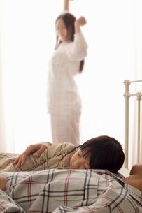 先に起きた母親と未だ寝ている娘と父親の写真素材 [FYI02069956]