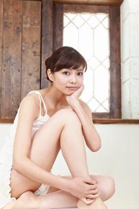 立て膝で座る若い女性の写真素材 [FYI02069981]