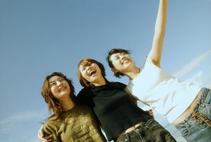 浜辺で肩を組む女性3人の写真素材 [FYI02069996]