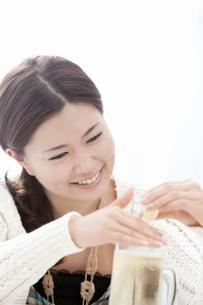 ジョッキのハイボールにレモンを搾る若い女性の写真素材 [FYI02069999]