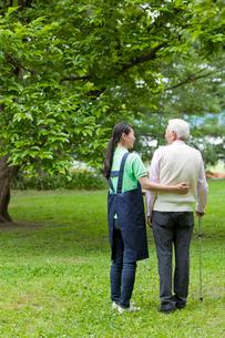 シニア男性と公園を散歩する女性介護士の写真素材 [FYI02070004]