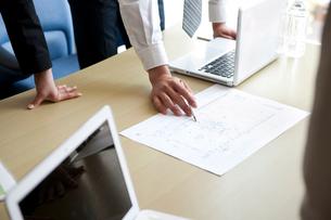 会議室で図面を見ながら打合わせをしているビジネスマン達の手元の写真素材 [FYI02070009]