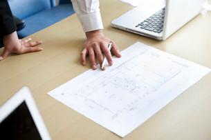 会議室で図面を見ながら打合わせをしているビジネスマン達の手元の写真素材 [FYI02070012]