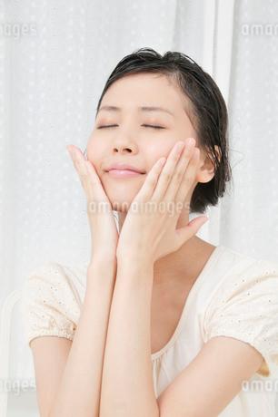 両手で顔をマッサージする若い女性の写真素材 [FYI02070015]
