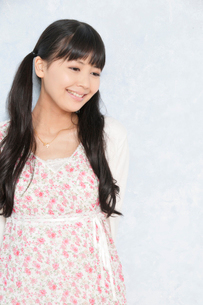 壁際で微笑む若い女性の写真素材 [FYI02070017]