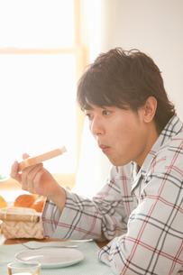 パジャマ姿で朝食をとる男性の写真素材 [FYI02070030]